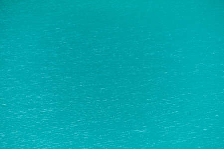 Shiny texture of azure surface of mountain lake. Minimalist background with reflection in clear water in sunny day. Copy space.