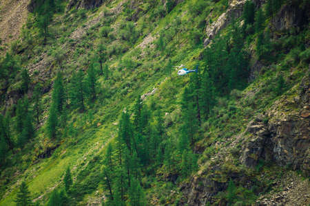 Helicopter in air against background of giant green rock covered with vegetation in tropical. Rescue mission in mountains. Aerial tourism in warm climate. Trees and grass on mountainside.