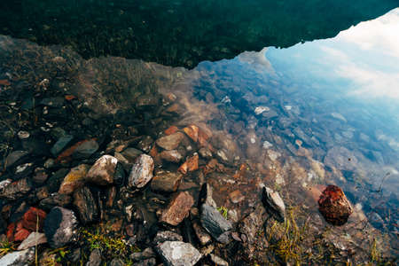 Plants and stones on bottom of mountain lake with clean water close-up. Giant mountain range reflected on smooth water surface. Background with underwater vegetation. Reflection of huge mountain ridge 写真素材