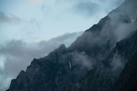 Ghostly giant rocks with trees in thick fog. Mysterious huge mountain with snow in mist. Early morning in mountains. Impenetrable fog. Dark atmospheric eerie landscape. Tranquil mystic atmosphere.