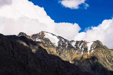 Snow on giant rocky ridge under blue cloudy sky. Dark steep mountainside. Amazing snowy mountain range in sunlight. Wonderful rocks. Atmospheric sunny landscape of majestic nature of highlands.