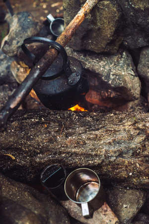 Boiling of tea in kettle on bonfire with large firewood. Tea drinking in open air. Active outdoor recreation. Camping in dusk. Romantic warm atmosphere in twilight on nature. Active rest. Metal mug. 写真素材