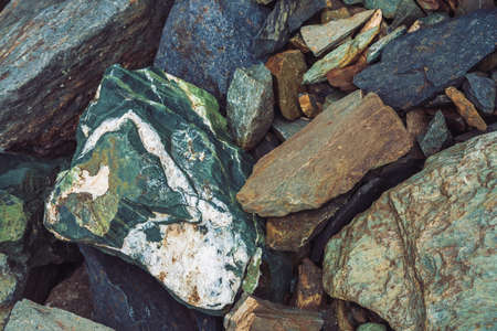 Multicolored boulder stream. Loose rock close up. Randomly scattered stones in nature. Amazing detailed background of highlands boulders with mosses and lichens. Natural texture of mountain terrain. Banco de Imagens