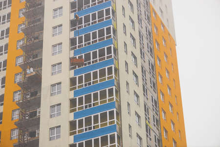 Concept of apartment building under construction close-up. Exterior of multicolor new multi-story residential building. Background with yellow walls, white plastic windows and blue loggias. Copy space