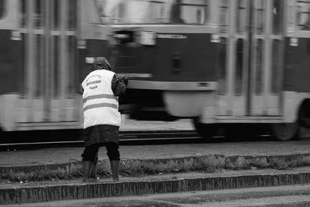 Street cleaner woman working in early morning. Laborer woman sweep street near tram rails. Janitor with broom dressed in worker vest. Streetcar motion blur. Russia, Barnaul, 31 July, 2014.