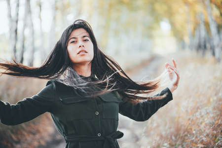 Dreamy beautiful girl with long natural black hair on bokeh background of autumn yellow leaves. Inspired girl enjoys nature in fall forest. Autumn euphoria. Female emotional portrait in faded tones.