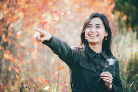 Dreamy beautiful girl with long natural black hair on autumn background with colorful leaves in bokeh. Inspired girl points finger away. Female beauty portrait among vivid foliage in autumn forest.