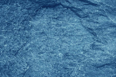 Vintage blue background. Rough painted wall of sapphire color. Imperfect plane of blue colored. Uneven old decorative toned backdrop of cyan tint. Texture of sapphirine hue. Ornamental stony surface.