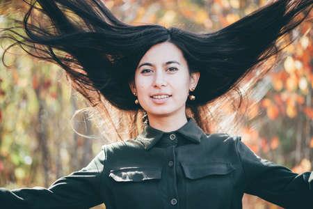 Retrato de belleza femenina rodeado de follaje vivo. hermosa chica de ensueño con largo cabello negro natural sobre fondo de otoño con hojas de colores en bokeh. Chica loca disfruta de la naturaleza en el bosque de otoño. Foto de archivo