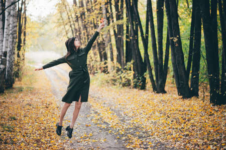 Dreamy girl with long natural black hair flies on autumn background with trees and yellow leaves in bokeh. Inspired girl enjoys nature in autumn forest. Beautiful girl jumps among fallen foliage.