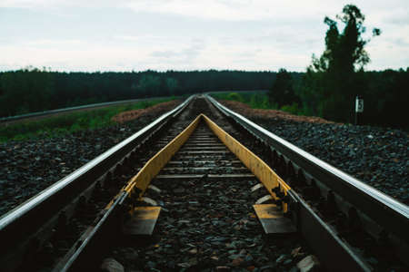 Dramatic scenery with railway in perspective and turn. Journey on rail track. Sleepers and rails close-up. Vanishing perspective. Receding lines. Landscape with railroad. Background with copy space.