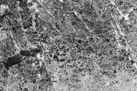 Vintage monochrome background. Rough painted wall of black and white color. Imperfect plane of grayscale. Uneven old decorative backdrop. Texture of black-white. Monochromatic ornamental stony surface Imagens