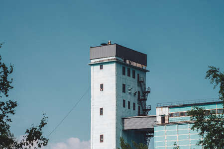 Giant tower of multistory production building. Picturesque old renovated working factory. Aged industrial object. Facade of big manufacturing high-rise building from trees. Industrial area close-up.
