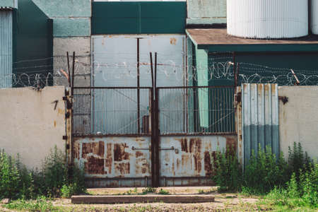 Picturesque industrial building close-up. Metallic rusty gate and concrete fence with barbed wire. Entrance in old factory. Closed area. Old industrial object is overgrown with grass. High metal doors
