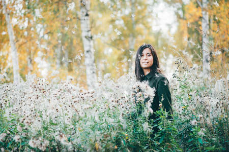 Dreamy beautiful girl in thistle thickets on bokeh background of yellow leaves. Inspired girl in white fluff in autumn forest. Female beauty portrait among flying spores of thistle.
