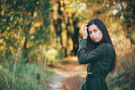 Female beauty portrait surrounded by vivid foliage. Dreamy beautiful girl with long natural black hair on autumn background with colorful leaves in bokeh. Inspired girl enjoys nature in autumn forest.