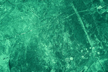 Vintage green background. Rough painted wall of emerald color. Imperfect plane of virid colored. Uneven old decorative toned backdrop of green tint. Texture of emerald hue. Ornamental stony surface.