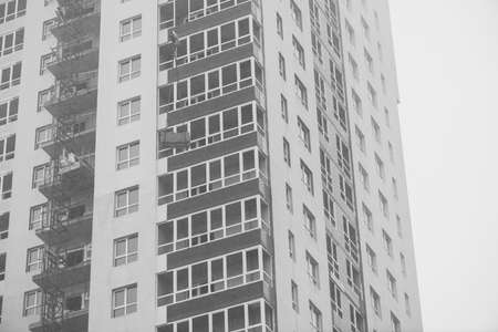 Monochrome concept of apartment building under construction close-up. Exterior of new multi-story residential building in grayscale. Background with walls, plastic windows and loggias. Copy space. 写真素材