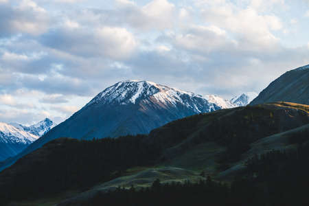 Atmospheric alpine landscape to snowy mountain ridge and forest hills in sunset. Snow shines in golden light on mountain peak. Wonderful scenery with beautiful shiny snowy top. Evening cloudy sky.