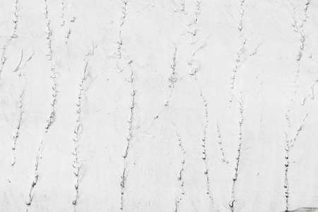 White textured nature background of snowy surface in mountains. Full frame of snowy cover with scratches. Natural background of snowbound mountain. White firn texture with cracks. Snow wall close-up. Фото со стока