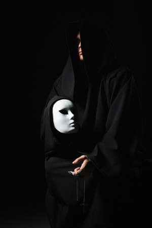 Rite of deal with devil. Sinner in black clothes and demon in sleeve. Man possessed by devil. Evil sorcerer talking with mask. Schizo speaks to himself. Cursed assassin in dark room. Vicious mage.