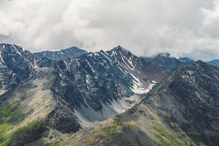 Atmospheric alpine landscape with big mountain ridge and snowbound peak in low clouds. Cloudy sky over huge mountain range. Giant snowy craggy rocks and rocky valley. Majestic scenery on high altitude