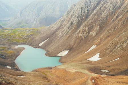 Atmospheric minimalist alpine landscape with beautiful glacial lake in highland valley among rocky mountains. Pieces of snow around mountain lake among stony rocky slope of glacier. Wonderful scenery.