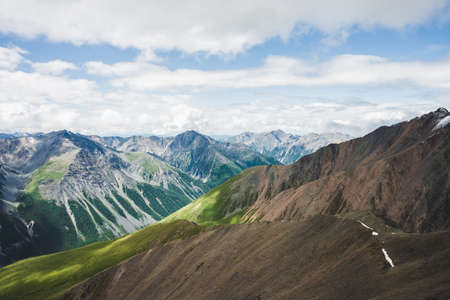 Aerial spectacular view to big beautiful mountains. Wonderful atmospheric alpine landscape with massive mountain ranges. Amazing wilderness nature of highlands. Majestic scenery on high altitude.