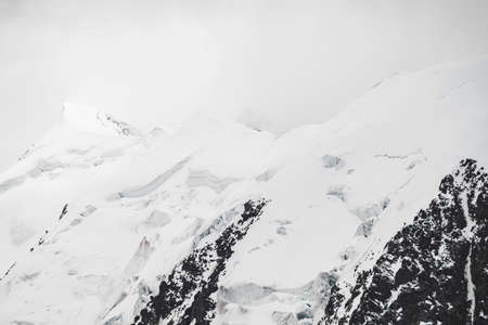 Atmospheric minimalist alpine landscape with massive hanging glacier on snowy mountain peak. Big balcony serac on glacial edge. Low clouds among snowbound mountains. Majestic scenery on high altitude. Stock Photo