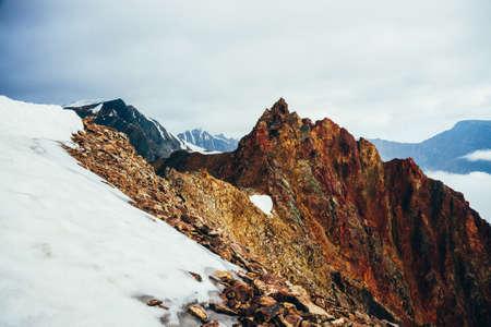 Beautiful pointed rocky pinnacle on giant snowy mountain. Vivid big pointy rocky peak. Atmospheric minimalist alpine landscape. Sharp rocky mountain top in cloudy sky. Wonderful highland scenery.