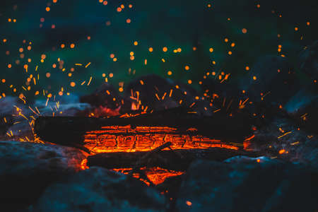 Vivid smoldered firewoods burned in fire closeup. Atmospheric background with orange flame of campfire. Wonderful full frame image of bonfire with glowing embers in air. Warm logs, bright sparks bokeh Stock Photo