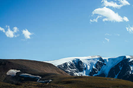 Awesome view to big snowy mountains behind green hill. Great glacier under blue sky. Wonderful vivid highland scenery with giant mountains with snow. Beautiful alpine landscape with glacial mountains. Standard-Bild