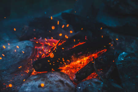 Vivid smoldered firewoods burned in fire close-up. Atmospheric background with orange flame of campfire. Unimaginable full frame image of bonfire. Glowing embers in air. Warm logs, bright sparks bokeh Stock Photo