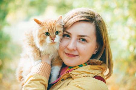 Beautiful autumn portrait of girl with big ginger cat in hands. Fluffy red cat in hands of woman in outdoor. Two lazy faces. Cute pet in hands on background of green orange bokeh. Big cat eyes closeup