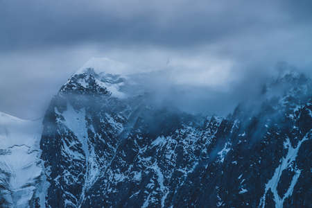 Bleak dramatic alpine landscape with glacier inside low clouds in dusk. Big mountain top with snow in cloudy sky in ghostly twilight. Atmospheric minimalist scenery with snowy rocks in dense fog.