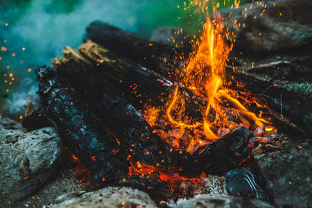 Vivid smoldered firewoods burned in fire close-up. Atmospheric background with orange flame of campfire and blue smoke. Warm full frame image of bonfire with glowing embers in air. Bright sparks bokeh