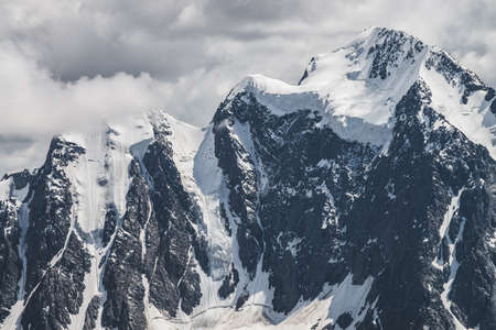 Atmospheric minimalist alpine landscape with massive hanging glacier on snowy mountain peak. Big balcony serac on glacial edge. Cloudy sky over snowbound mountains. Majestic scenery on high altitude. 스톡 콘텐츠