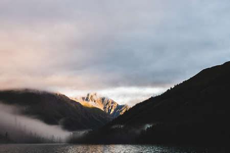 High gold mountain peak and many low clouds above mountain lake at sunrise. Dense fog above water and forest in golden hour. Atmospheric highland landscape at early morning. Alpine relaxing scenery.
