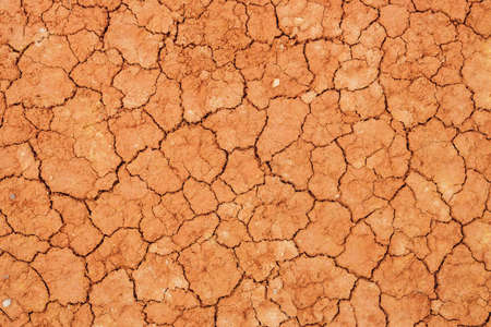 Nature background of cracked dry lands. Natural texture of soil with cracks. Broken clay surface of barren dryland wasteland close-up. Full frame to terrain with arid climate. Lifeless desert on earth 스톡 콘텐츠