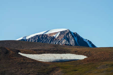 Giant snowy mountain behind green hill with big piece of firn. Great glacier under blue sky. Wonderful sunny highland scenery with huge mountain with snow. Beautiful minimalist alpine landscape.