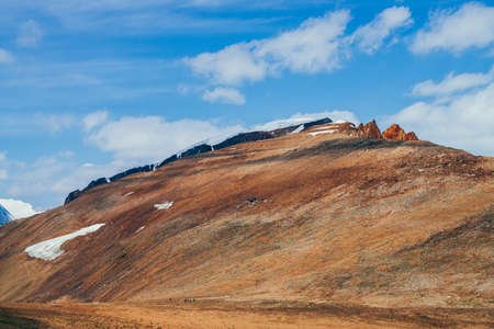 Awesome sunny mountain with red orange brown crags in top under blue sky. Colorful stony hill with snow in sunshine. Wonderful alpine scenery with rock in red color. Beautiful vivid highland landscape 스톡 콘텐츠