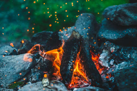 Vivid smoldered firewoods burned in fire close-up. Atmospheric background with orange flame of campfire. Full frame image of bonfire. Warm whirlwind of glowing embers and ashes in air. Sparks in bokeh 스톡 콘텐츠