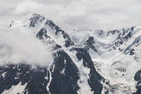 Atmospheric minimalist alpine landscape of big snowy mountain with massive glacier. Low cloud among great rocky mountains. Glacier tongue near snowbound mountainside. Majestic scenery on high altitude