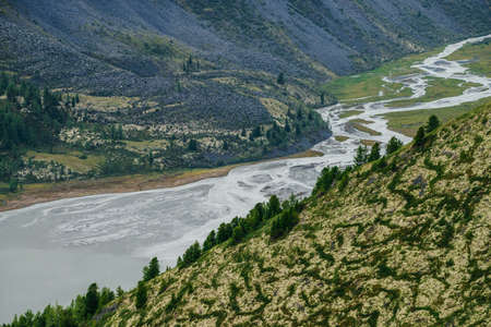 Awesome aerial view to beautiful valley with mountains lake and giant textured hillside. Atmospheric alpine scenery with big rocky hills and huge mountains. Trees on mountainside with nature patterns.