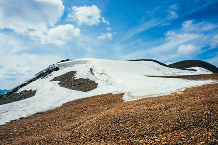 Beautiful small glacier with ice cornice on stony hill under cloudy sky. Snow on mountain. Firn on rock. Atmospheric alpine scenery on high altitude. Wonderful highland landscape of majestic nature. Stock Photo