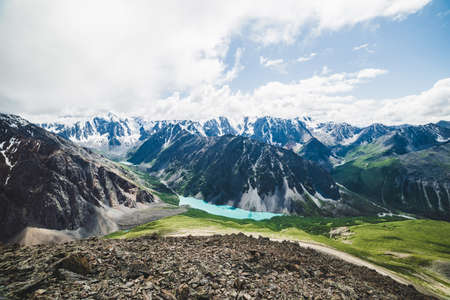 Spectacular view to scenic valley with big beautiful mountain lake surrounded by giant snowy ranges and glaciers. Amazing atmospheric highland landscape. Wonderful majestic wilderness nature scenery.