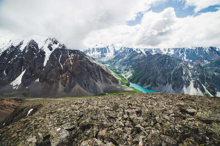 Spectacular view to scenic valley with big beautiful mountain lake surrounded by giant snowy ranges and glaciers. Amazing atmospheric highland landscape. Wonderful majestic wilderness nature scenery. Stock Photo