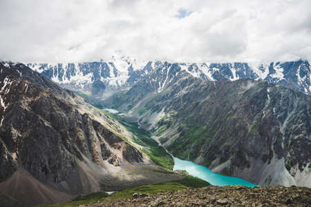 Spectacular view to scenic valley with big beautiful mountain lake surrounded by giant snowy ranges and glaciers. Amazing atmospheric highland landscape. Wonderful majestic wilderness nature scenery. Stock fotó