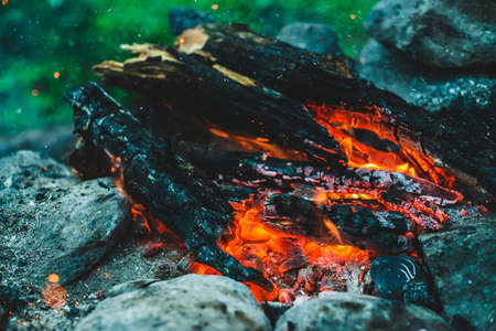 Vivid smoldered firewoods burned in fire closeup. Atmospheric background with orange flame of campfire. Full frame image of bonfire with sparks in bokeh. Warm vortex of glowing embers and ashes in air 스톡 콘텐츠