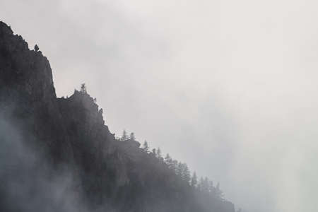Dramatic bleak fog among giant rocky mountains. Ghostly atmospheric view to big cliff in cloudy sky. Low clouds and beautiful rockies. Minimalist scenery in mysterious place at early foggy morning. 스톡 콘텐츠